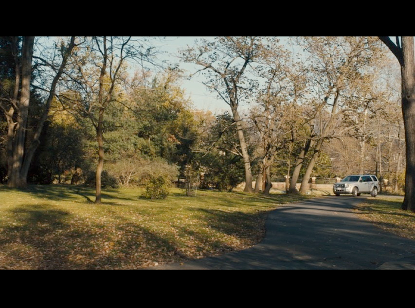 Screenshot of Philomena and Martin driving up the long driveway leading to Peter Olsson's house (the Conways' Potomac house in real life).