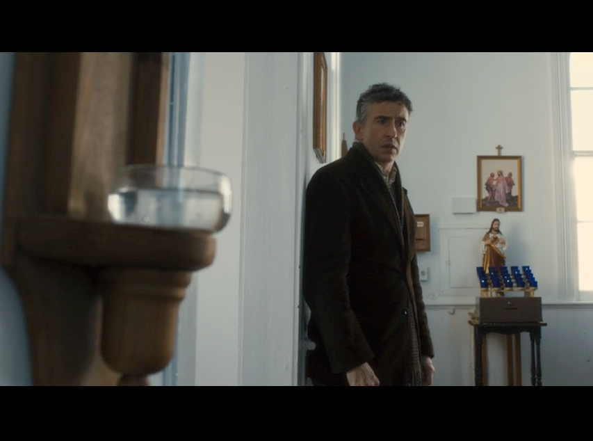 Screenshot: Martin standing inside St. Paul's Community Church where the production team added religious elements to turn it into a Catholic church, including the font of holy water featured in the foreground.