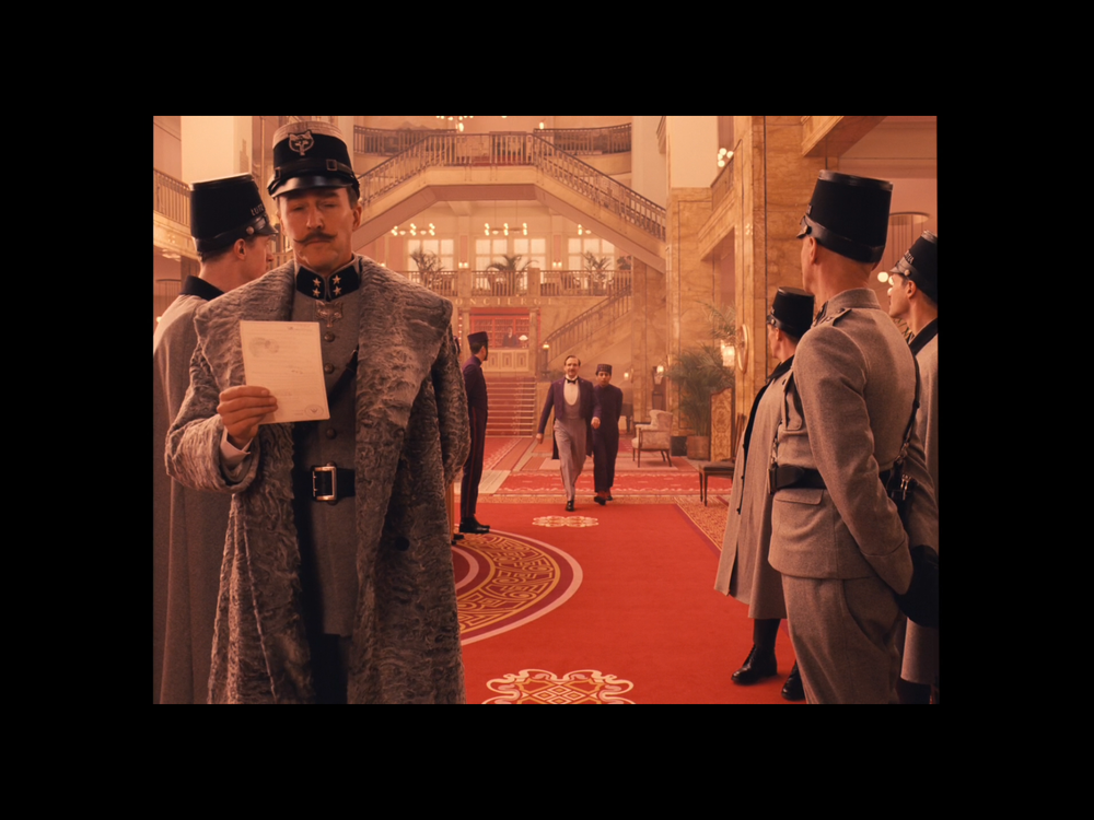 A screenshot from the movie of a scene in the lobby of Grand Budapest Hotel during its pinnacle time in the 1930's - with Henckels in the foreground waiting for M. Gustave (who's followed by Zero). The film location of the above scene was also the Görlitz Warenhaus Department Store.