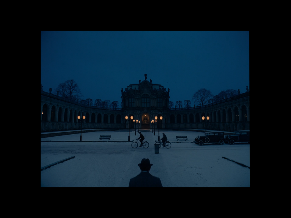 Screenshot of a scene with Deputy Kovak walking toward the Kunstmuseum (filmed at the Zwinger Museum in Dresden, Germany).