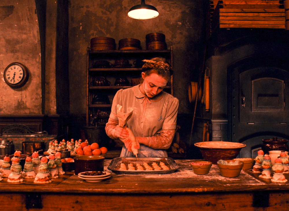 Production still of Agatha putting on the finishing touch on the beautiful pastries of Mendl's  - image via  Google .