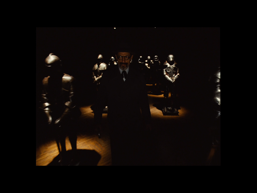 Screenshot from the movie featuring Deputy Kovacs rushing through the Hall of Armours in the Kunstmuseum, filmed at The Stadhalle.