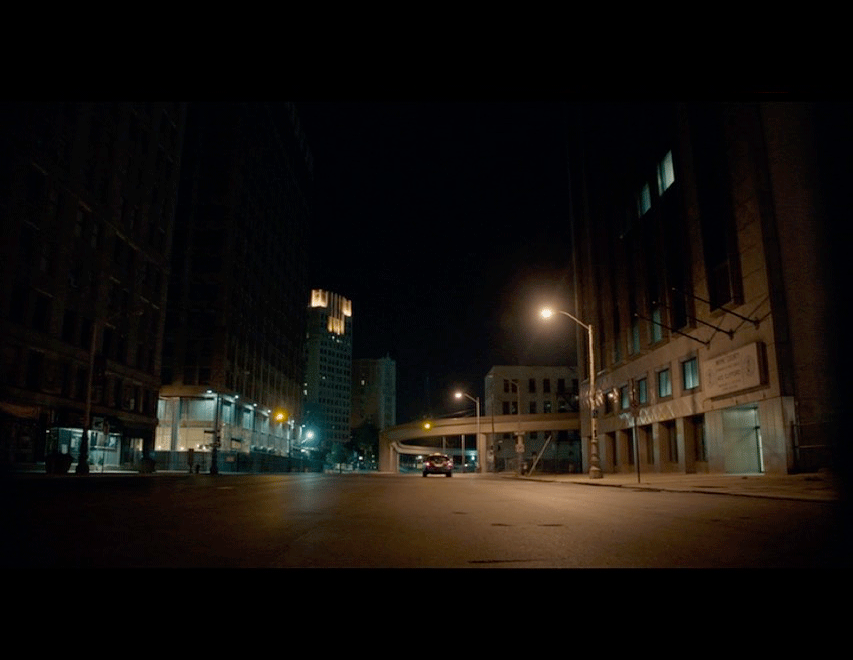 Screenshot from the movie of Eve's cab as it drives through the empty streets of Detroit.