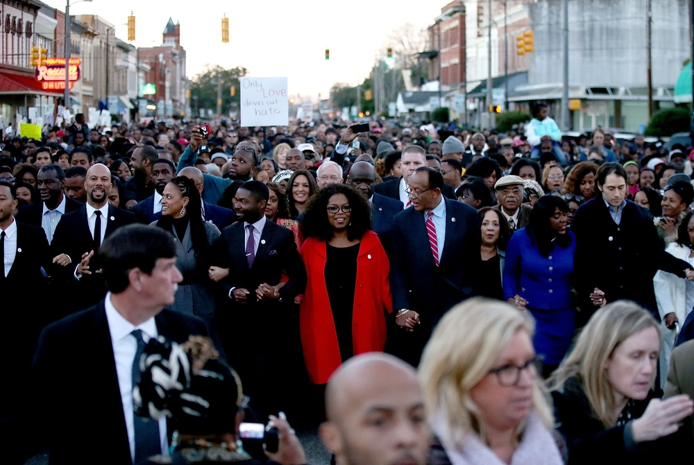 Oprah Winfrey and the cast of Selma walk down Broad Street towards the Edmund Pettus Bridge accompanied by thousands of participants in honor of Rev. Martin Luther King Jr. Day on January 18, 2015 in Selma, Alabama. (Photo by Sean Gardner/Getty Images)
