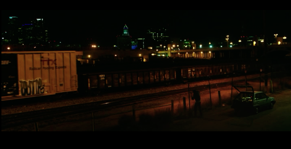 Screenshot from Nightcrawler of a scene at the beginning at the movie at the train track with the Los Angeles skyline twinkling in the background.