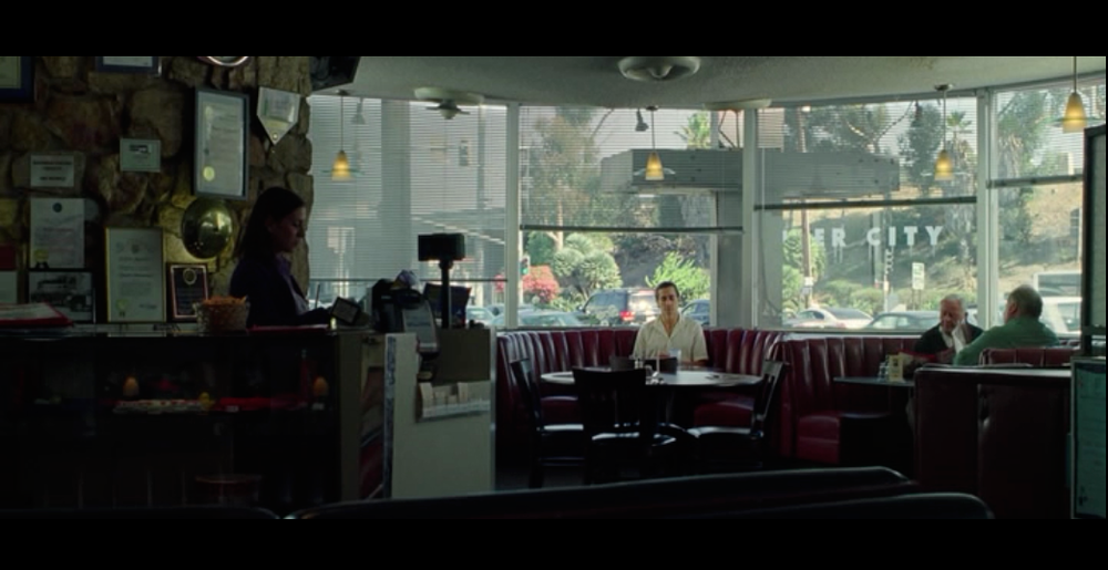 Screenshot from Nightcrawler of a scene filmed at Dinah's Family Restaurant. The wide open windows behind the booth provides a great view of the L.A. life outside - one of the reasons why Dinah's is a popular film location.