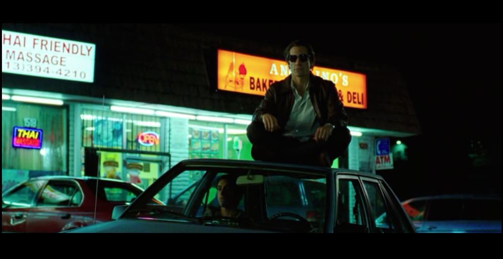 Screenshot from Nightcrawler of a scene filmed in front of Angelino's Bakery on West Sunset Blvd - featuring Lou Bloom sitting on top of his car and Rick (his employee/intern) sitting inside the car - both waiting for a crime to happen so they can be first to cover it.