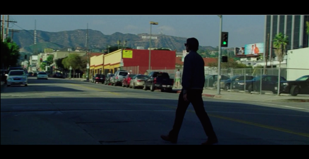 Screenshot from Nightcrawler of Lou Bloom crossing the street after he leaves the police station - the Hollywood sign in the far background quietly reminds us of Los Angeles as the other main character in the film.