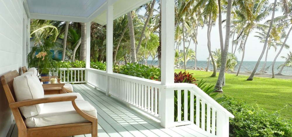 One of the distinctive cottage verandas of the Moorings Village & Spa with views of the private, palm-lined beach - image via the resort's website.