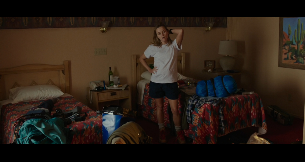 Screenshot of Cheryl (Witherspoon) in a motel room in The Mojave Desert area feeling overwhelmed as she puts her backpack together to get ready for the PCT hike. Filmed on location at the Courtesy Inn Motel in Portland, Oregon.