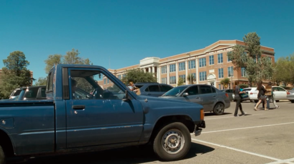 Screenshot from Boyhood of a scene filmed at Sul Ross State University featuring Mason Jr. as he parks his truck in the parking lot of the school.