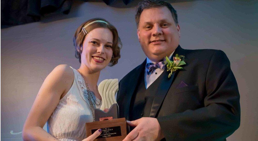 2016 EMERGING ARTIST WINNER KELSEY GILKER, LEFT, RECEIVES HER AWARD FROM MAYOR PETER MILOBAR. | IMAGE: KAMLOOPS THIS WEEK