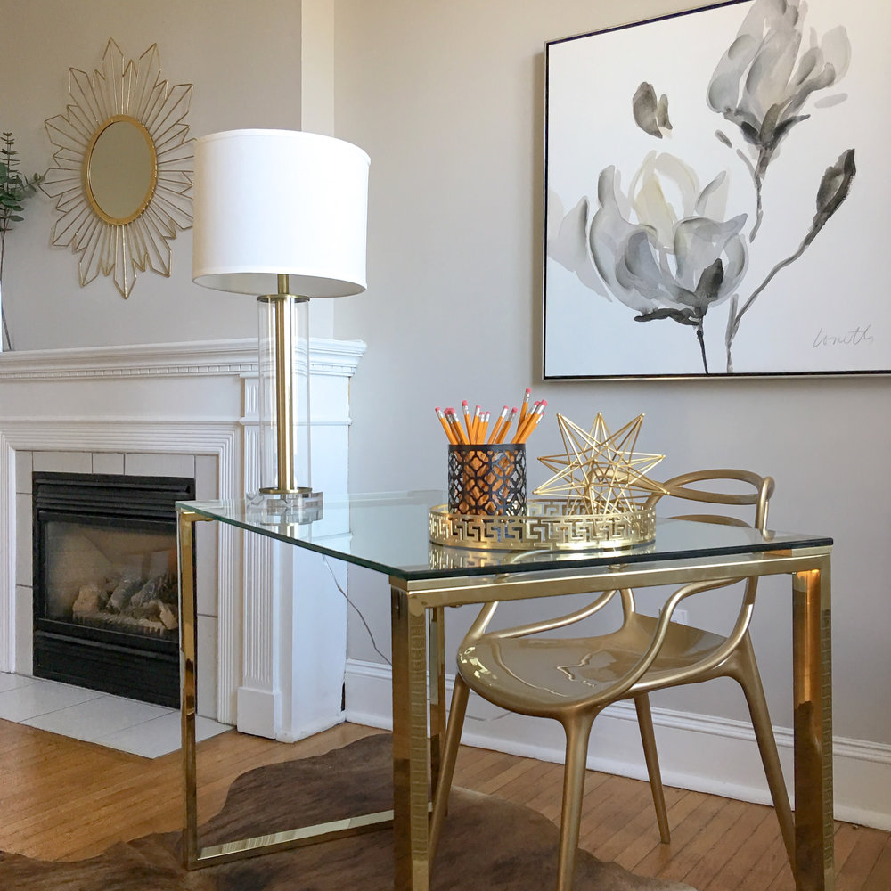 Luxury home staging in Aurora. Gold and glass desk paired with neutral statement art.