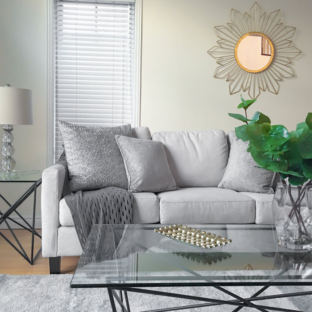 Home Staging provided by New Leaf Decor of living room in Barrie-Neutral furniture accented by warm gold and greenery.