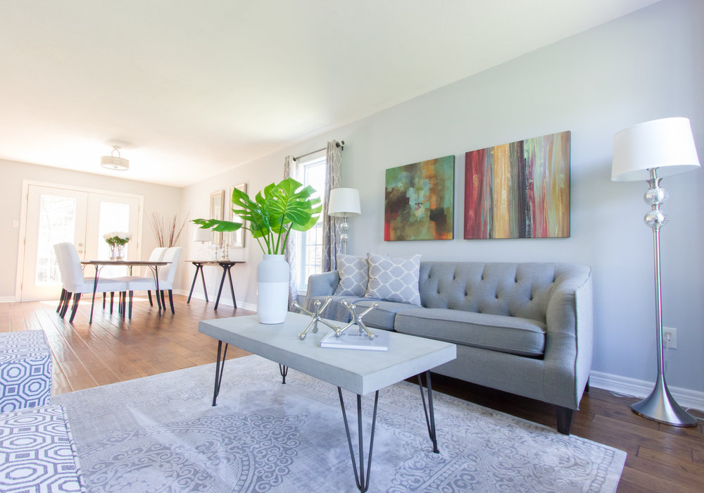 Home Interior Staging by New Leaf Decor. Living room staged with statement artwork and neutral furniture accented by greenery