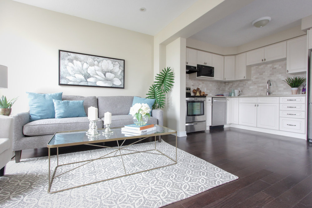 Home Staging provided by New Leaf Decor of living room - neutral furniture with pops of colour add appeal