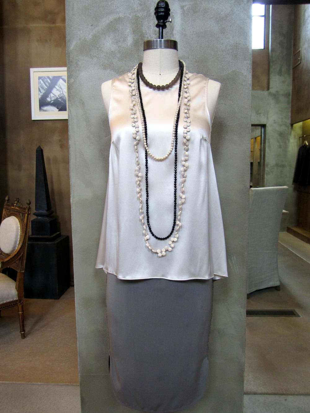 Brunello Cucinelli Reversible Sleeveless Silk Top with Monili Back Detail. Vanilla. $795. Available in Medium, Large and X-Large. Silk Pull-On Skirt with Monili Athletic Detail. Military. $1210. Available in 4, 6, 8. Double Strand Long Necklace in River Stone, Black Agate and Smoky Sand. $1150. Long River Stone Necklace. Vanilla. $1195. Made in Italy.