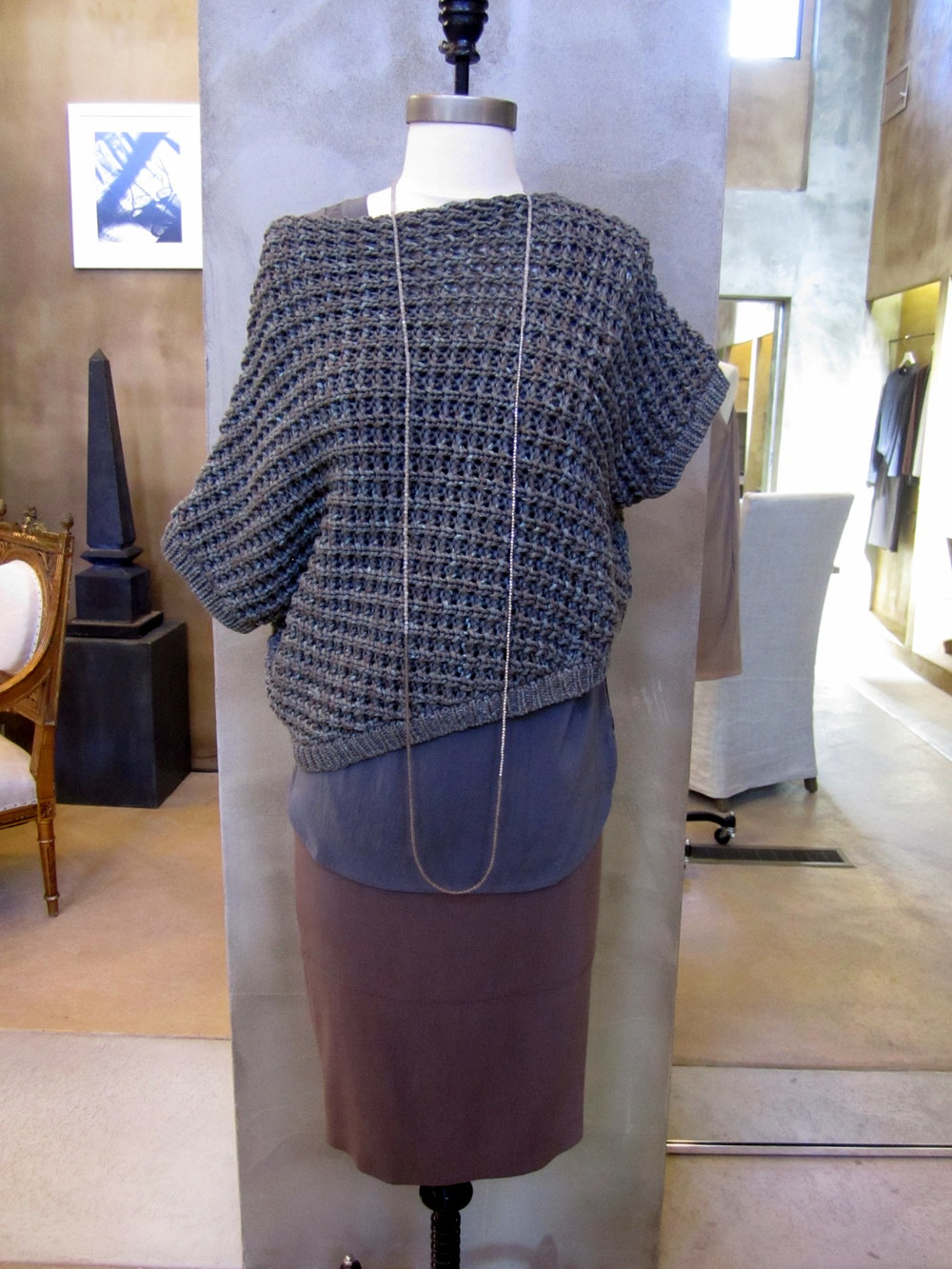 Brunello Cucinelli Cotton Chunky Knit Open Weave Pullover. Army. $1120. Available in Medium and Large. Reversible Silk Scoop Neck Top. Marine. $795. Available in Medium, Large and X-Large. Silk Skirt with Leather Panel Detail. Bark. $1130. Available in 6, 8 and 10. Long Necklace in Moonstone, Sanded Quartz and Brown Grey Zebra. $725. OSFA. Made in Italy.