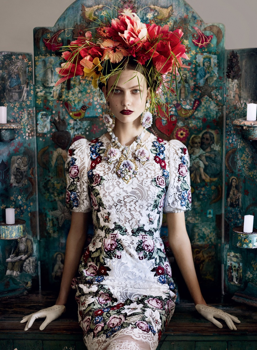 "Vogue's newly released editorial features a a modern figure of striking resemblance to the renowned Mexican painter, Frida Kahlo.  Vogue's ""Frida"" poses in from of an antique style painted wood candelabra screen, poised perfectly in a lace floral dress, donned in an exaggerated version of the artist's signature floral headdress, accessorised by oversized drop earrings and a necklace, each a bouquet of roses backed with lace and garnished with pearls.//""Frida"" de Vogue pose à partir d'un écran de candélabres bois peint de style antique, prêt parfaitement à une robe en dentelle florale, enfilée dans une version exagérée de coiffeflorale de signature de l'artiste, accessoirisée de grandes boucles d'oreilles et un collier, chacun un bouquet de roses soutenu avec dentelle et garni de perles."