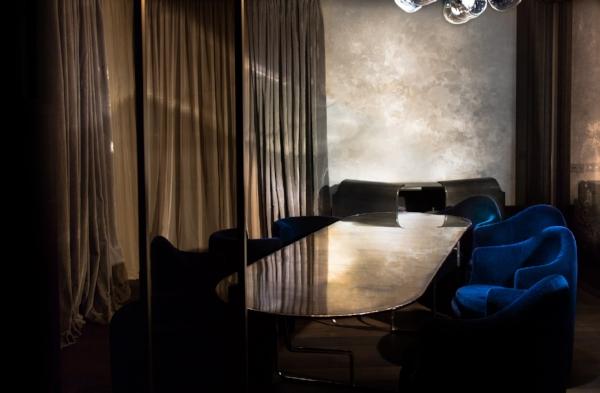 In the dining area, a Lindsey Adelman chandelier hangs above a De Cotiis bespoke silver plated table arranged with cashmere blue velvet chairs by Luigi Caccia Dominioni. To the rear rests the Armour brass faced sideboard by Privatiselectionem.//Dans la salle à manger, un lustre de Lindsey Adelman est suspendu au-dessus d'une table à manger sur mesure argentée plaquée par De Cotiis , arrangée avec fauteuils de Cachemire velours bleu par Luigi Caccia Dominioni. À l'arrière le buffet Armour de face en laiton par Privatiselectionem.