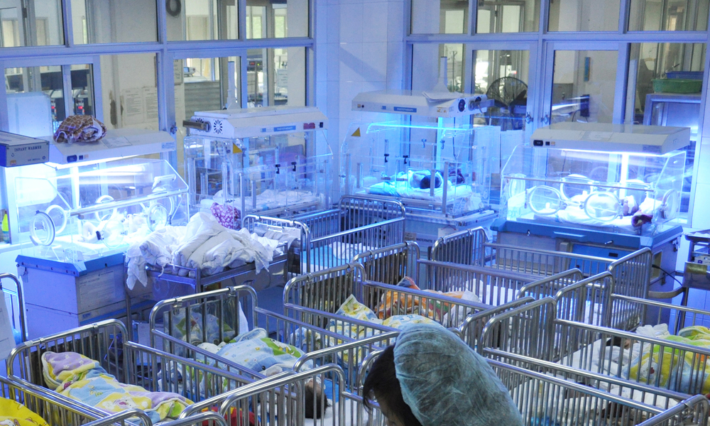 Don't be fooled by the phototherapy lamps shining from above; the four nonworking incubators that sit along the walls are used only as hard to clean beds for the well-baby room at a national hospital in Vietnam.
