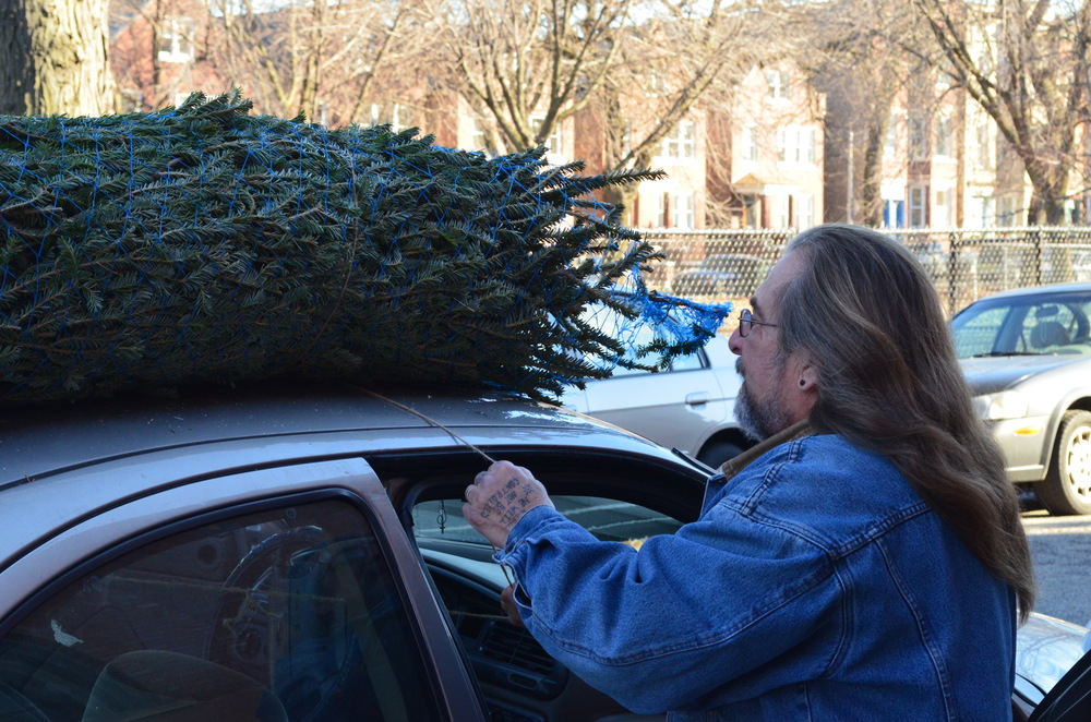 Benton House neighbor Bob Klee helps a family load their tree