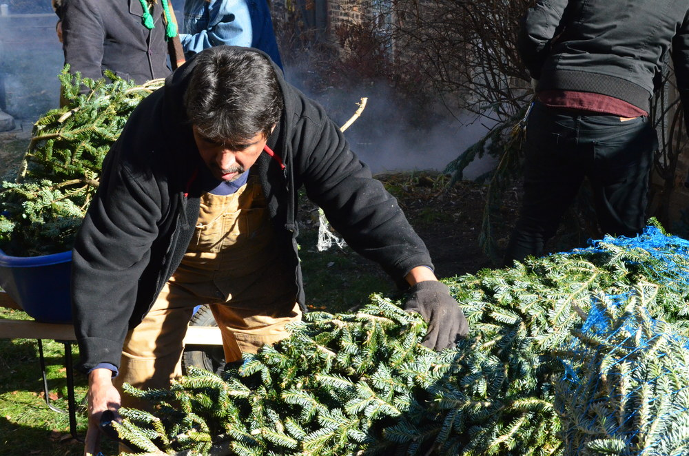 Paul Martinez unpacks and trims donated trees