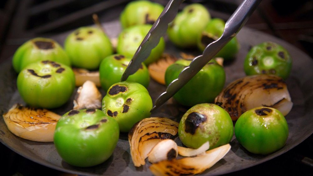 Dry roasting tomatillos, onion, and garlic on a comal