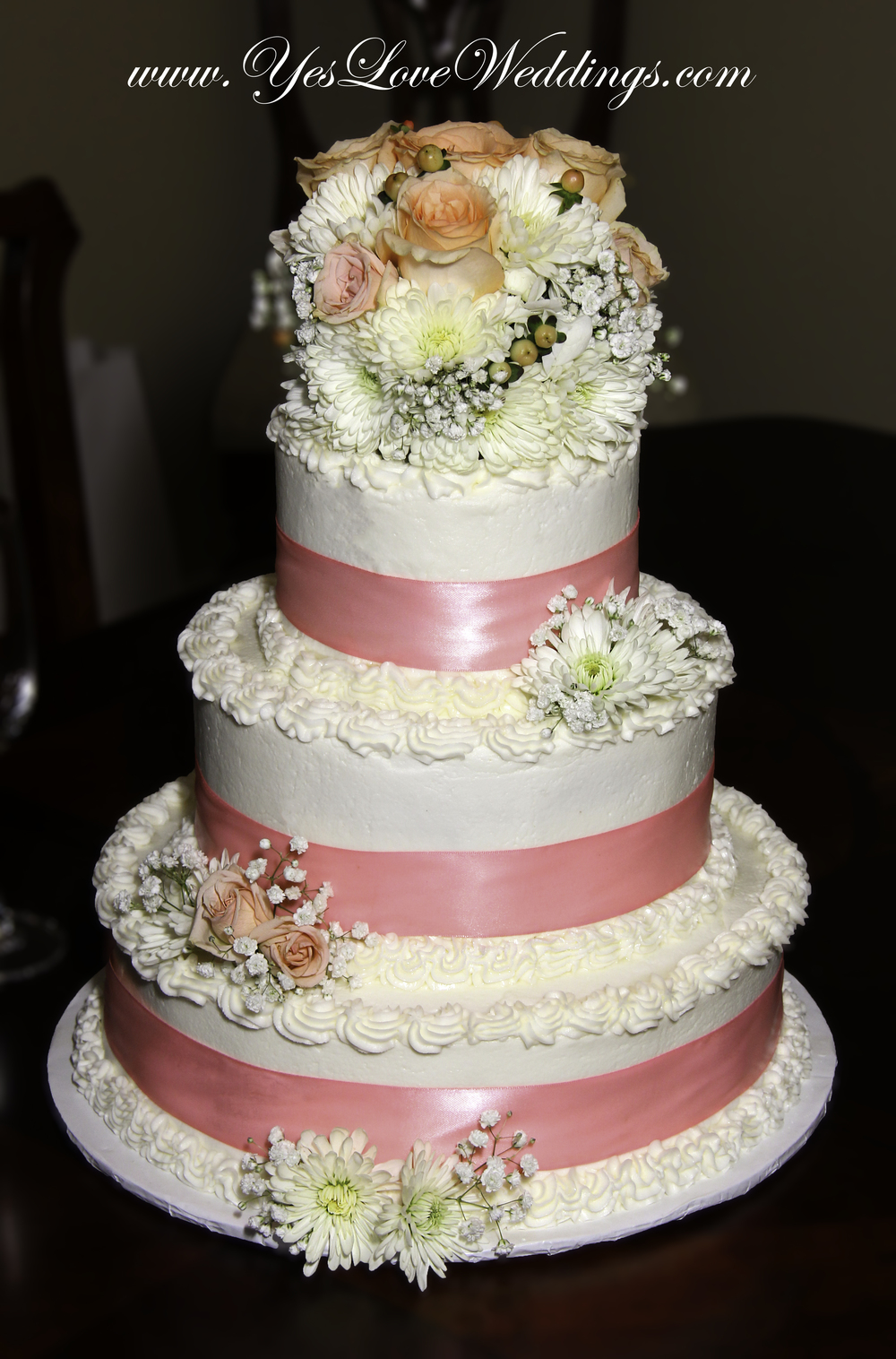 Pink three tier wedding cake with roses