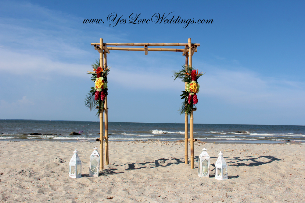Bamboo arch beach wedding with tropical flowers
