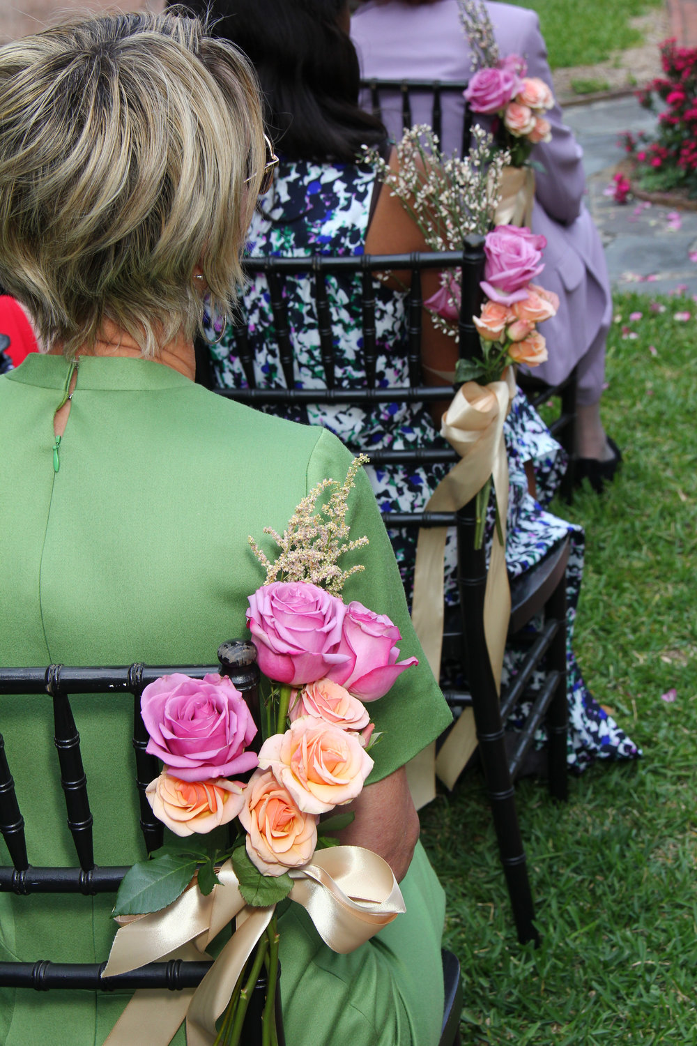 Roses in purple and peach with gold ribbon decorate wedding chairs Savannah wedding Davenport Garden