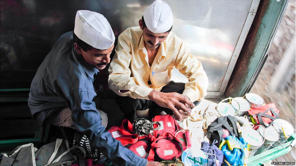 The dabbawalas confirm the numbering of the tiffin boxes during their train ride. (BBC)