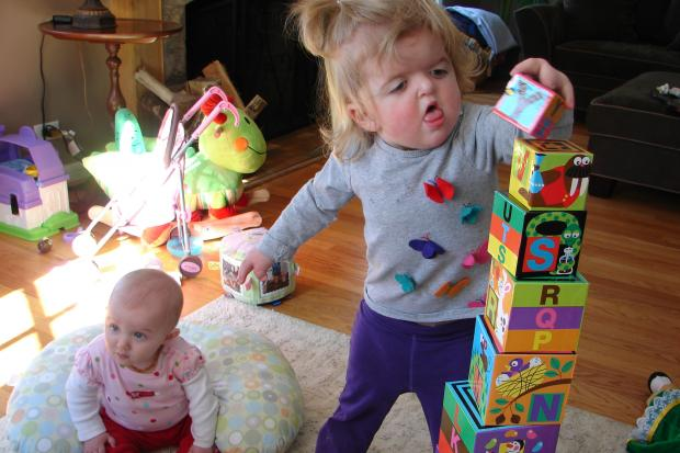 Mary Cate Lynch, 2, of Beverly stacks blocks alongside her 6-month-old sister Maggie. Mary Cate has Apert syndrome, which doesn't stop a playful, sibling rivalry between the two sisters.