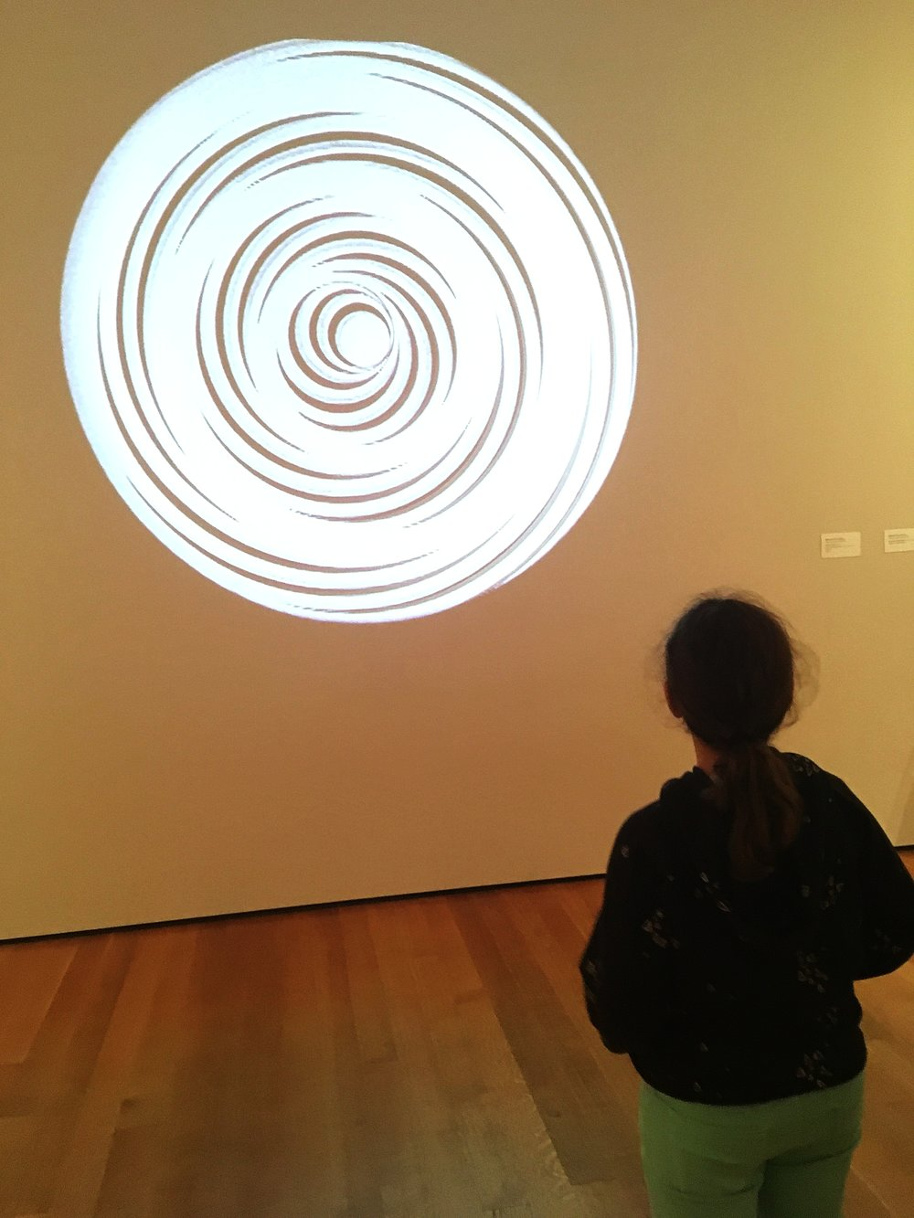 Child looks at projected art.