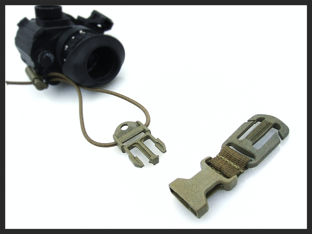 The optional Dummy Cord Clip interfaces with MOLLE webbing  creating a secondary point of attachment for added security when the optic is stored in a pouch.