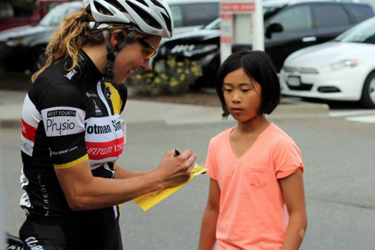 Alison signs her autograph for a future bicycle racer.