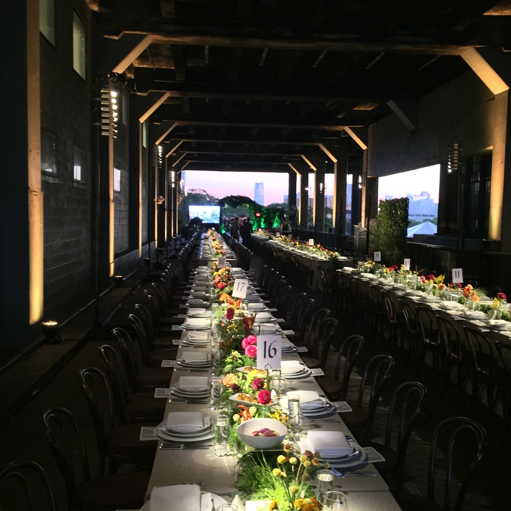 Two long tables are set for the evening with the event floral design created by Van Wyck & Van Wyck.