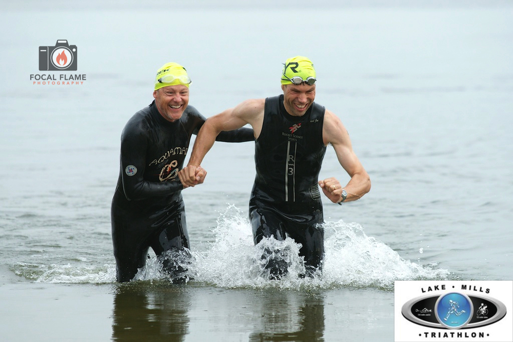 Klaas van Zanten (right) emerges from the water at the Lake Mills Triathlon supported by his friend Jay Handy (left). (c) 2014 Focal Flame Photography. Photo credit: Josh Zytkiewicz