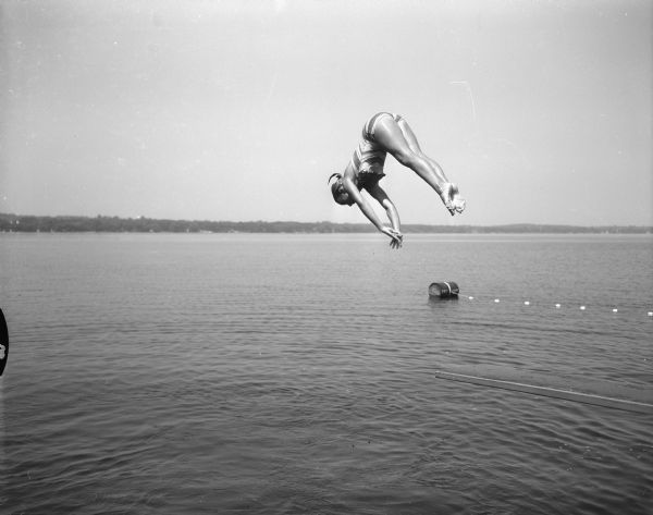 "Caption on a photo dated July, 1955, reads, ""Tia Nelson, 11, daughter of Mr. and Mrs. Russell Nelson...dives into Lake Mendota. She was one of Madison's most outstanding young swimmers."""
