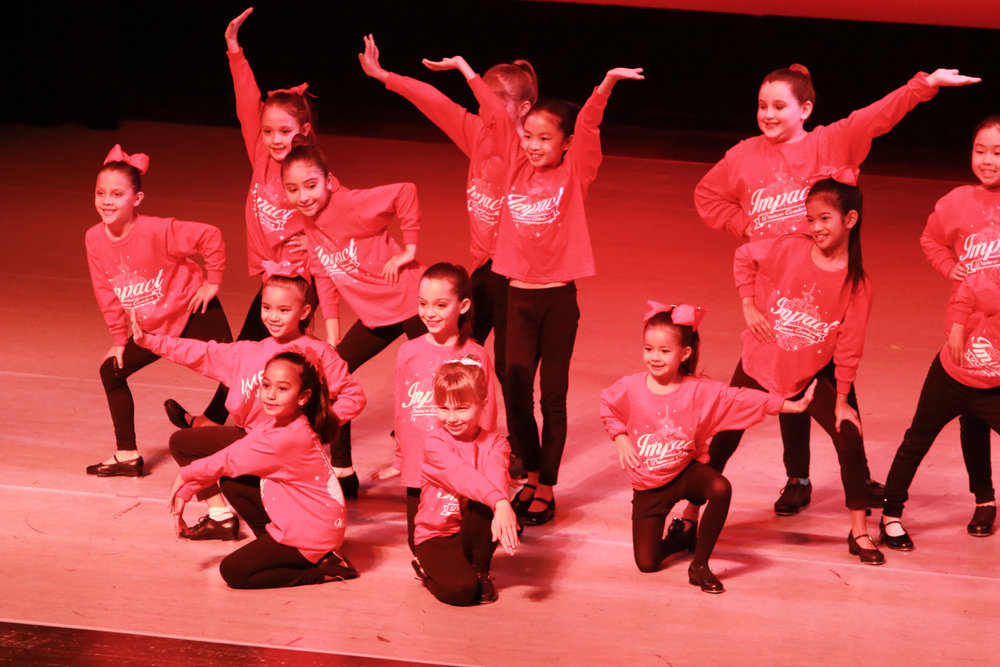 Impact Dance Center students hit their ending pose during a performance