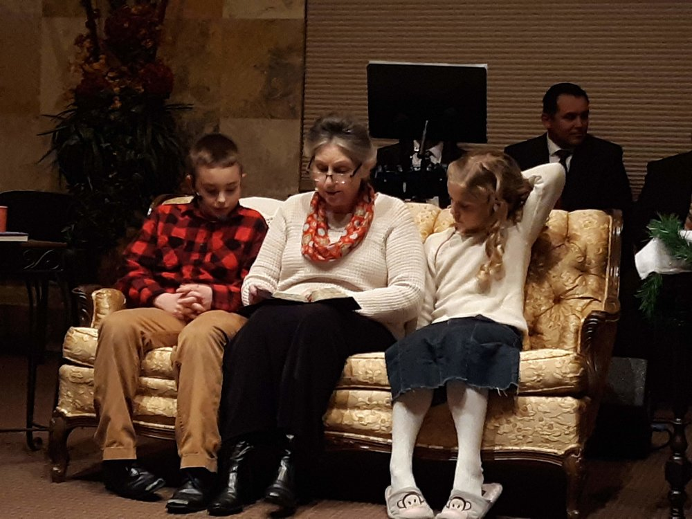 Sis. Cynthia, as Grandma, reads the Christmas Story to Dallas and Mandy