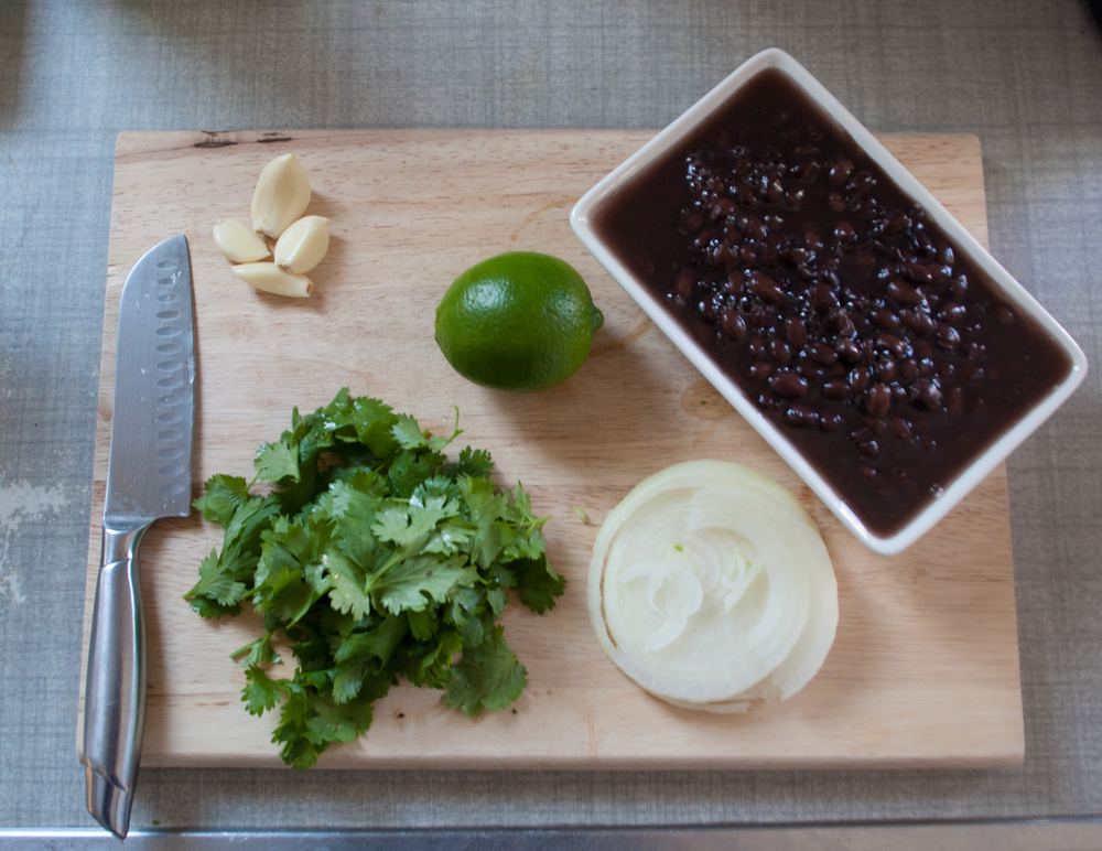Let's talk about ingredients first.  Bean dip-  2 cans of black beans  4 garlic cloves- minced  3 lime wedges  1 quarter of an onion-chopped  1 handful of cilantro-chopped  1 teaspoon of sugar  Olive oil  Salt and Pepper to taste  For the chips-  Veggie oil- Enough to fry your tortillas  Tortillas- I use flour, cut into quarters