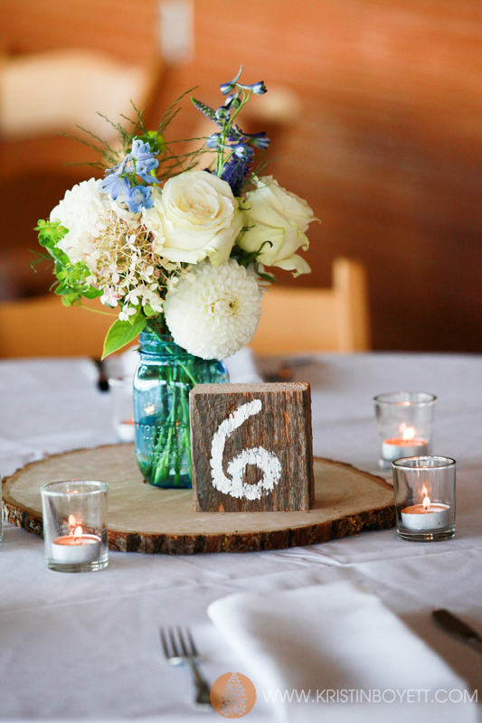 """Christina and Britten wanted to use blue mason jars on wood for the centerpieces. Each table received a """"cabin number""""."""