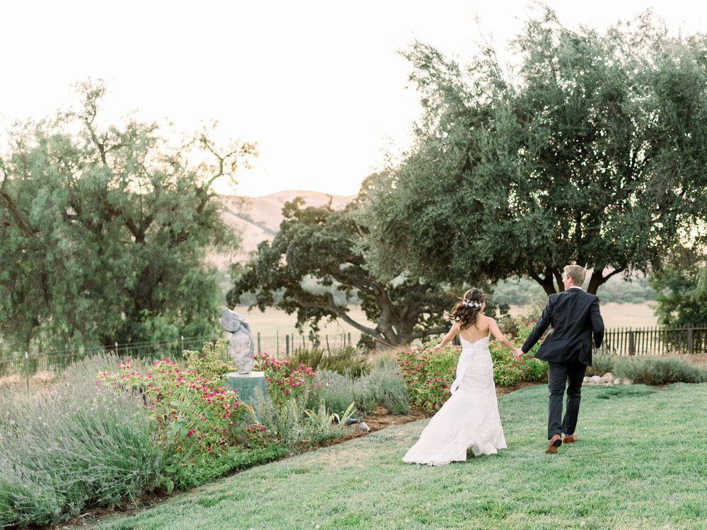 bride-and-groom-running-through-the-grass-at-sunset.jpg