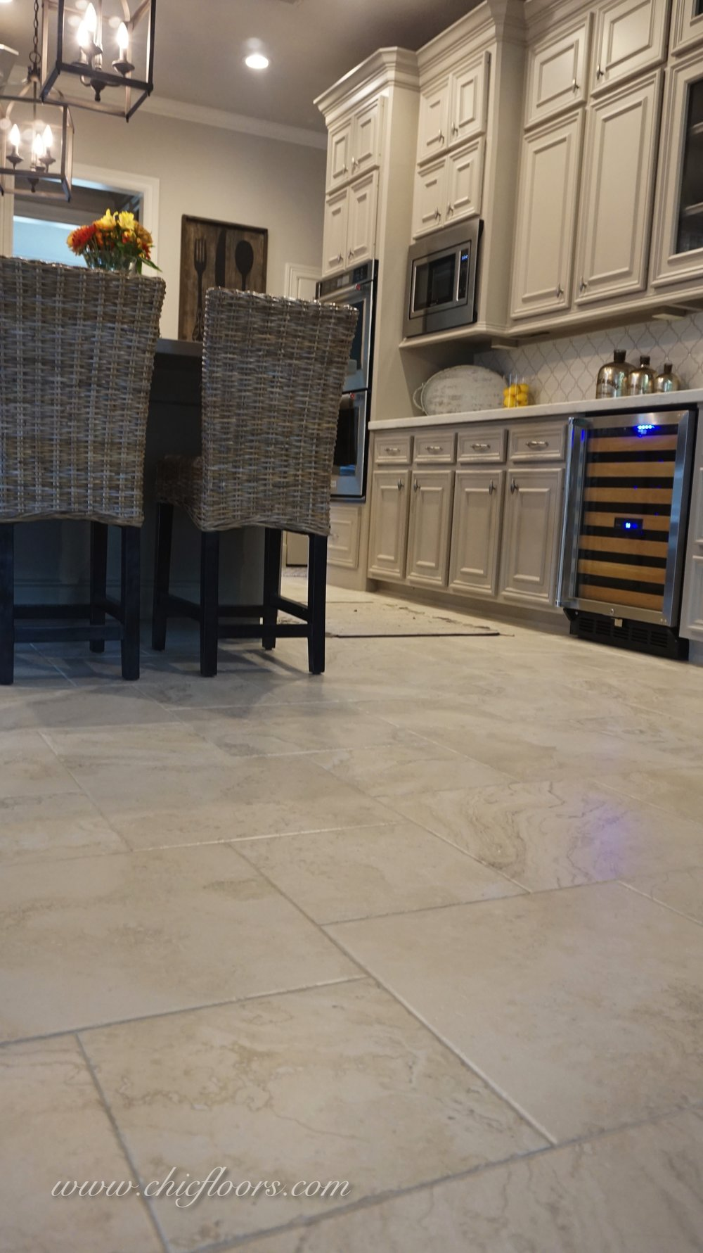 The 18x18 tile pulls together the light gray cabinets, the darker gray island, and the brown island stools.