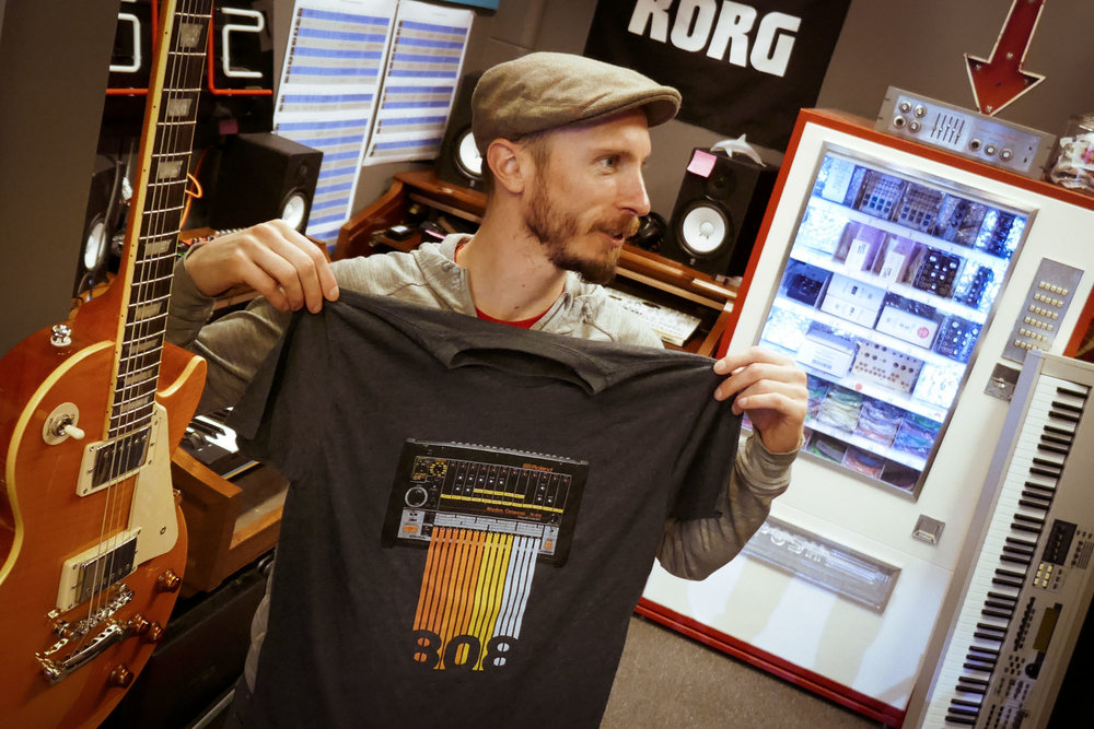 Matthew Fit examines a Roland 808 T-Shirt.