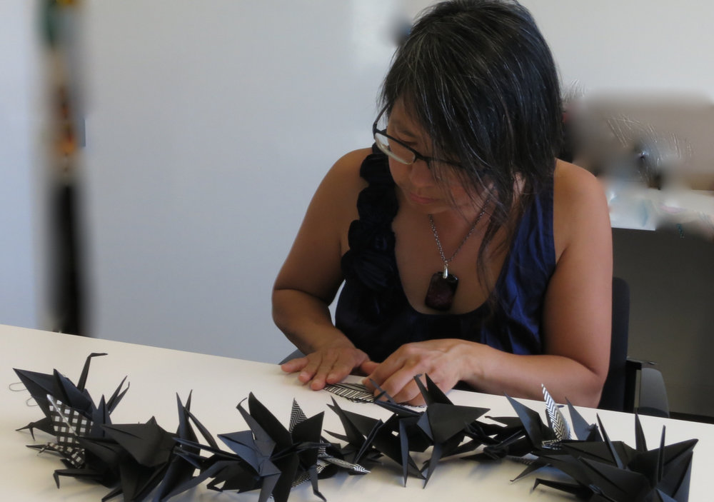 Artist folding cranes for 1000 Gifts of Decolonial Love, 2016. Photo credit: Lana Lin