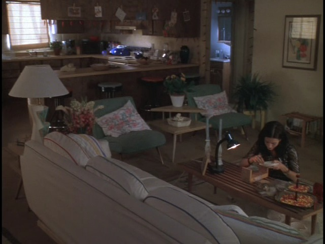 Another view of Karina (Courteney Cox) in the living room of Edward's crummy Vegas apartment stage set.