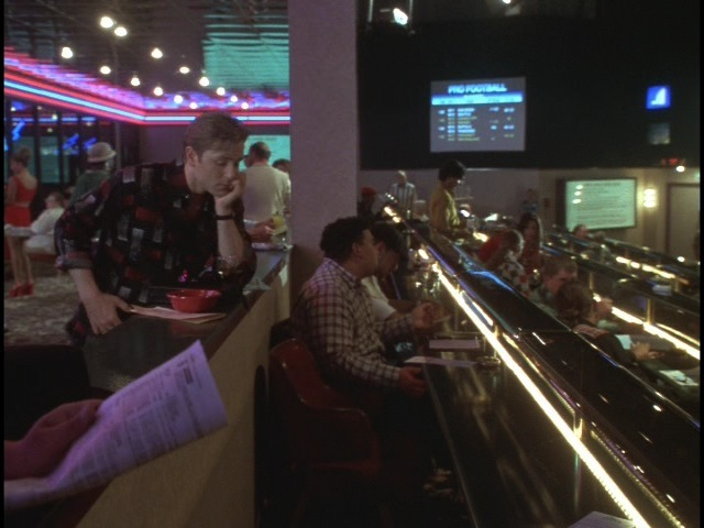 Edward (Ron Eldard) watching his fortunes slip away at the asino sports book betting tables.