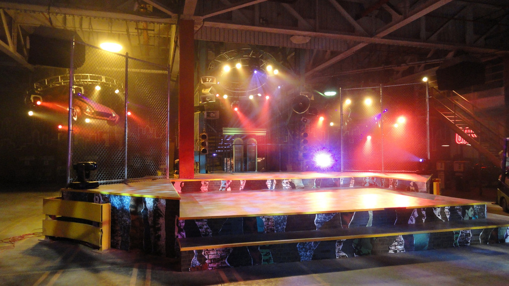 "Even more of the story takes place in a teen hip hop club called Off the Street. Thematically we chose to play on that name and create a huge, de-constructed ""street"" as a safe space for a young crowd to meet, dance, and compete. The set was built in an enormous, abandoned auto manufaturing plant, which gave us the opportunity to incorporate some of it's amazing industrial goodness. This is the main rap-battle stage and DJ booth."